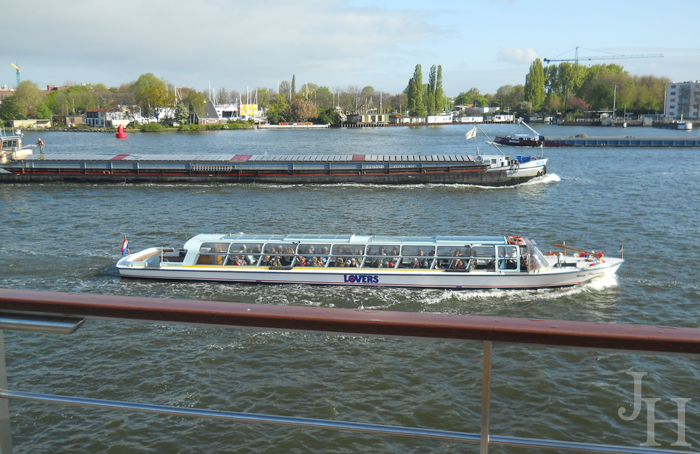 The many barges and tour ships in the Rhine in Amsterdam