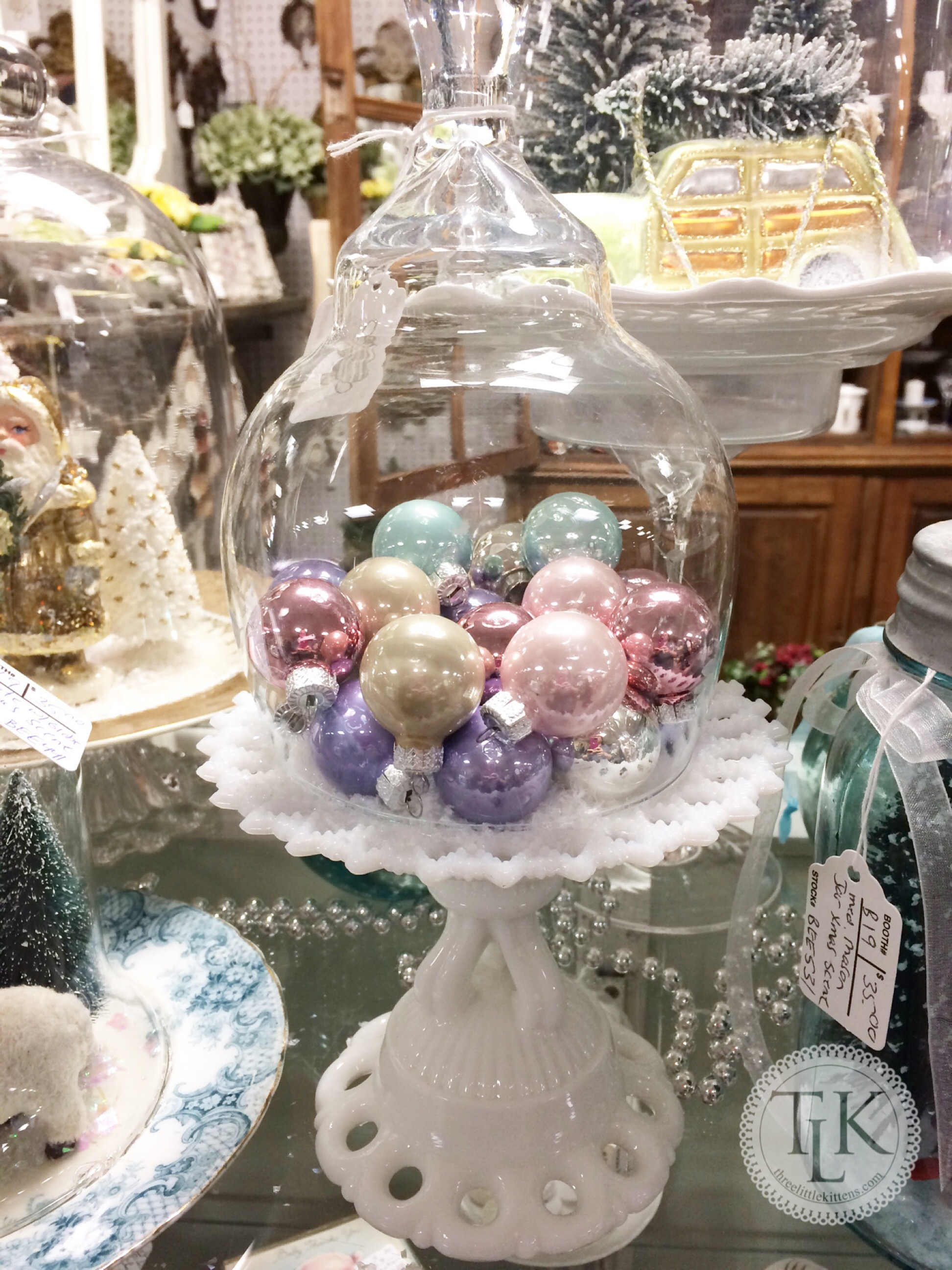 cake plate of pastel ornaments under a cloche